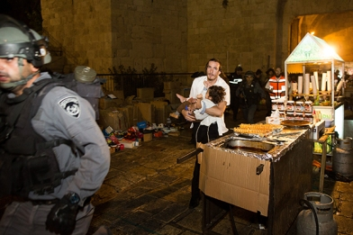 A Jewish man carries a baby injured in a stabbing attack in the Old City of Jerusalem on October 3, 2015. A Jewish family was stabbed while walking near the Lion's Gate in the Old City. The father died of his wounds. The terrorist was shot down by police. Photo by Yonatan Sindel/Flash90